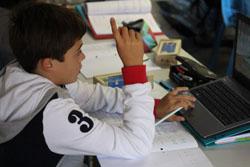 Afbeelding van een jongen met laptop in de klas.