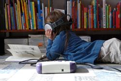 Afbeelding van een meisje voor een boekenrek dat naar een boek luistert en tegelijk in een boek bladert.