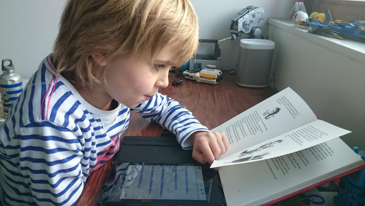 Foto van Sid, die het Daisy-boek beluistert op zijn tablet en tegelijk meevolgt in het gedrukte boek.