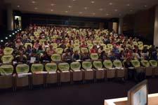 Mensen nemen plaats in de zaal voor de studievoormiddag