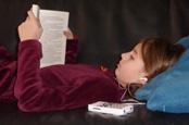 Meisje leest een boek terwijl ze met een Plextalk Pocket mee luisterleest