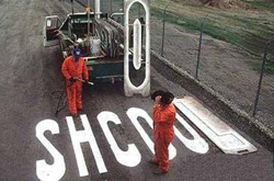 afbeelding van gemeentewerkers die de wegmarkering 'school' verkeerd geschreven hebben.